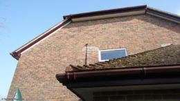 White soffit with rosewood bargeboards and brown square guttering Winchester